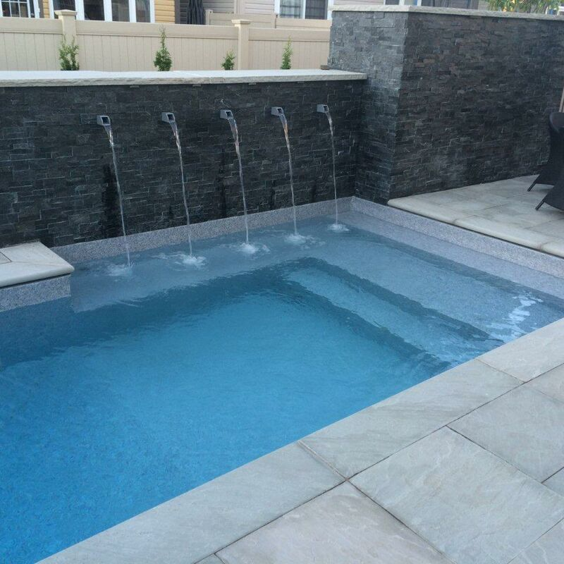 Water features built into a retaining wall flowing into a swimming pool