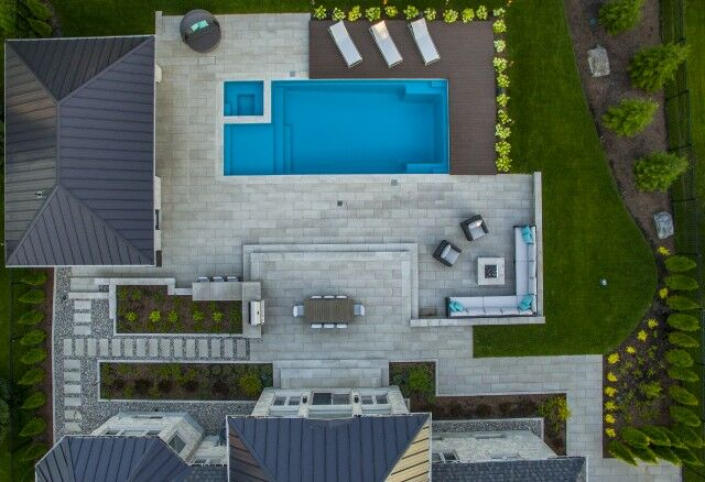 birds eye view of resort like residential backyard landscape design pool, hot tub, interlock patio,  wood sunning deck with sun loungers