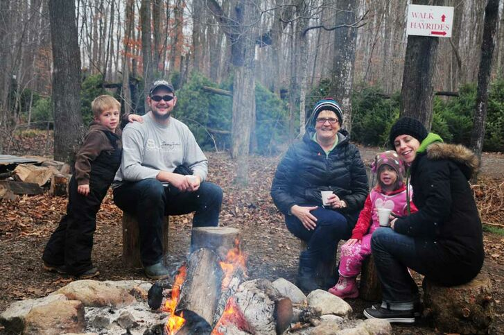 Family and friends around a fire with hot chocolate, Thomas Tree Farm