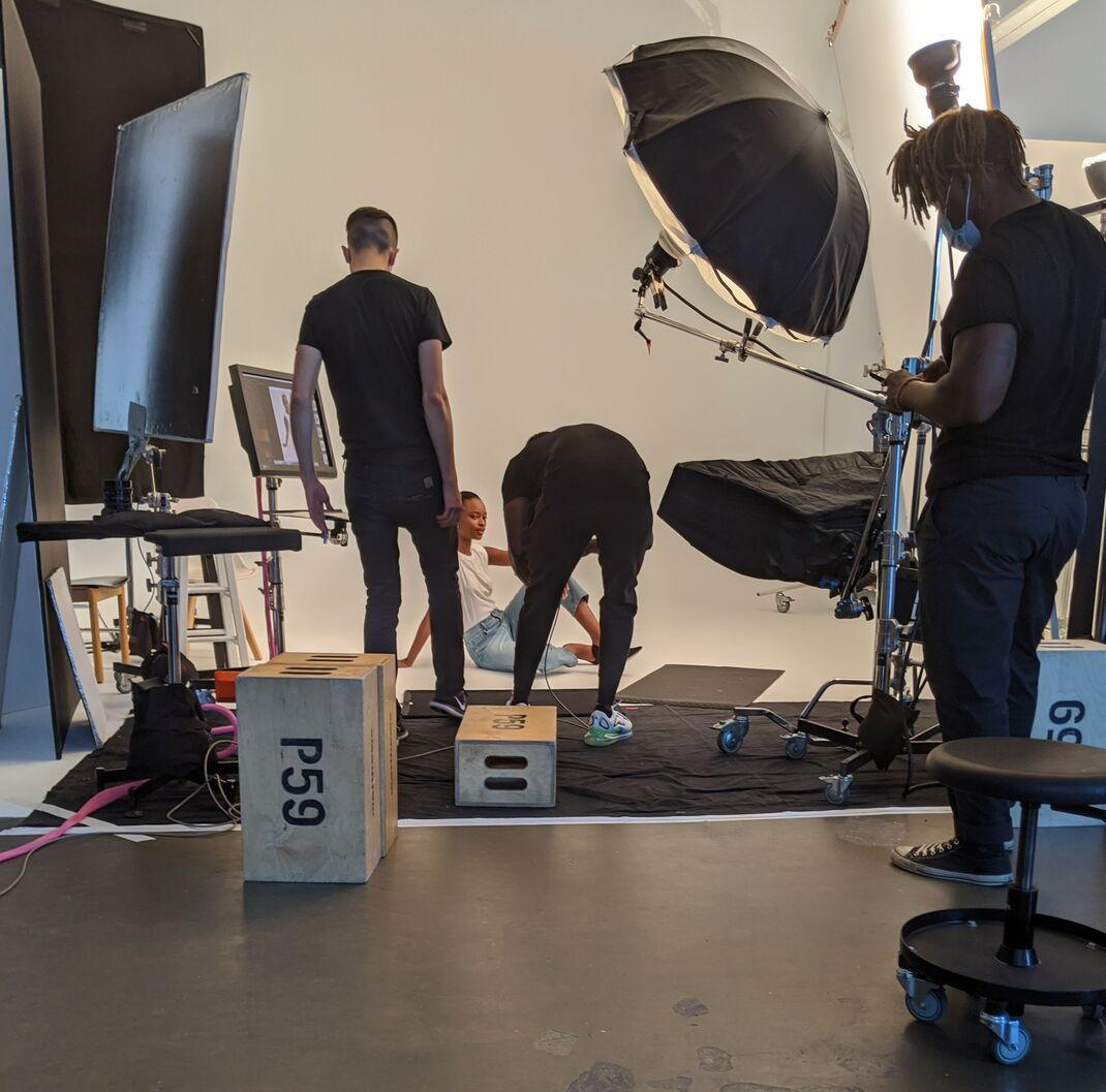 Photographer and assistants photographing model for high street fashion brand.
