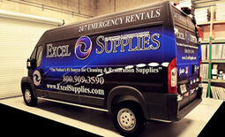A fully wrapped van in blue and black with the Excel Cleaning & Restoration Supplies logo on the side.