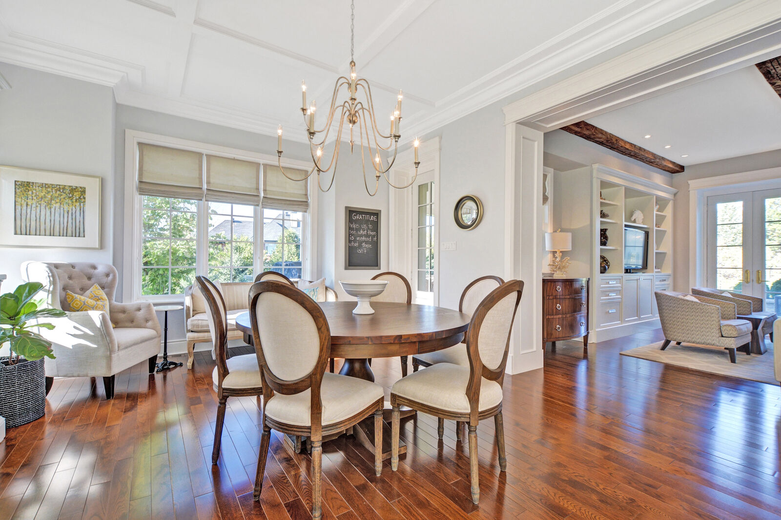 An eat-in dining area with-in a transitional style kitchen. a small window seat with a fiddle-lead fig plant in the corner, hardwood floors and custom moulding.