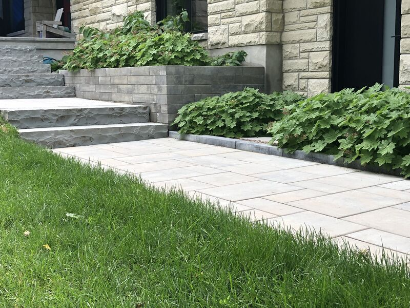 interlock pathway leading to front porch on corner property with banas stone natural steps and  interlock edger and lushes geranium plants