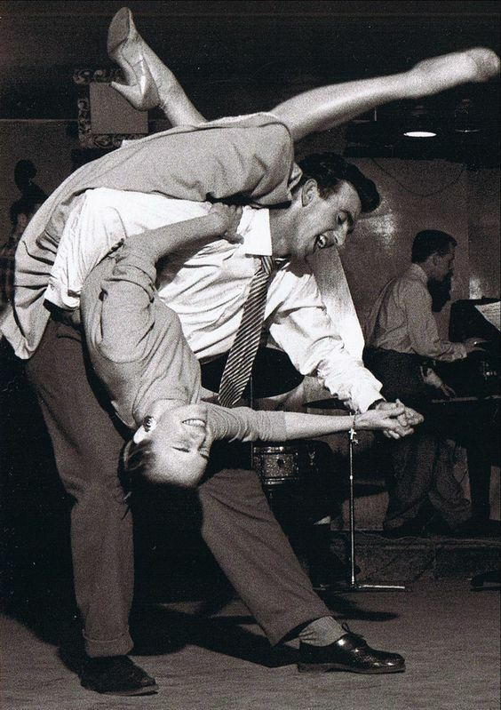 This is a classic vintage foto of a young couple dancing to rock 'N' Roll or Jump jive music in a club in the 50's