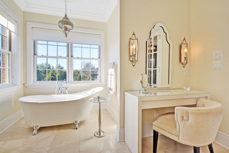 Transitional style master bathroom with stand alone claw-foot tub,  make up vanity, Moroccan style pendant light and large windows