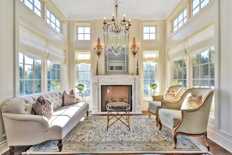 traditional living room area with large windows, roman shades, custom marble fireplace mantel and surround with beveled mirror above and flanking sconce lighting