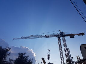 two tower cranes lifting elements of Potain MC80