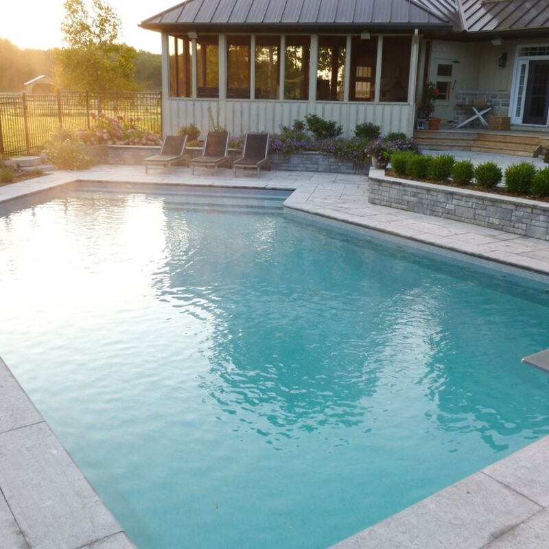 Custom designed backyard swimming pool with small waterfall feature