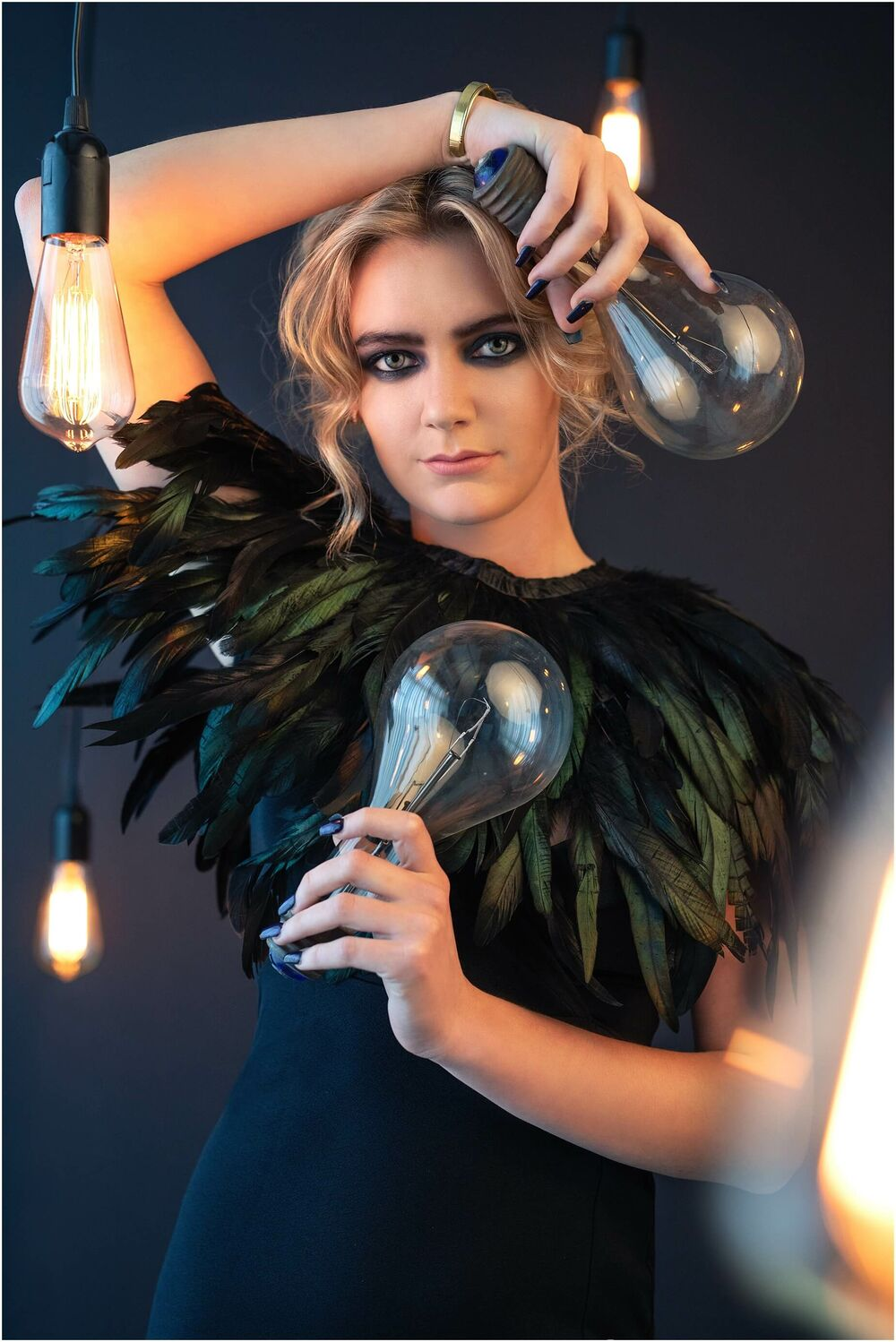 fashion portrait of beautiful girl in black feathers surrounded by vintage lightbulbs