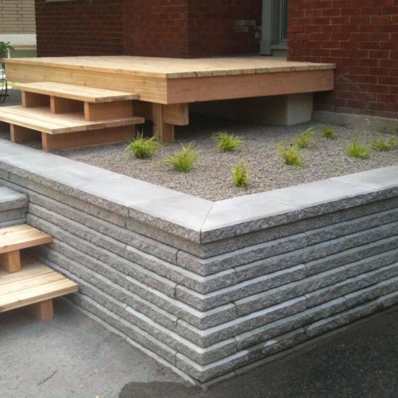 Wooden landing with steps onto a retaining wall