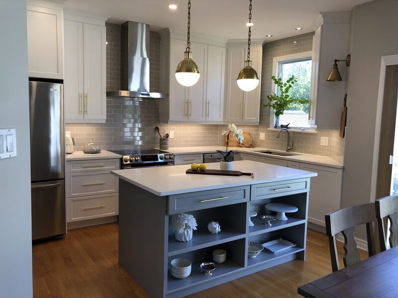 kitchen with stainless steel appliances, modern hood fan, brass fixtures and open shelving in taupe coloured  island