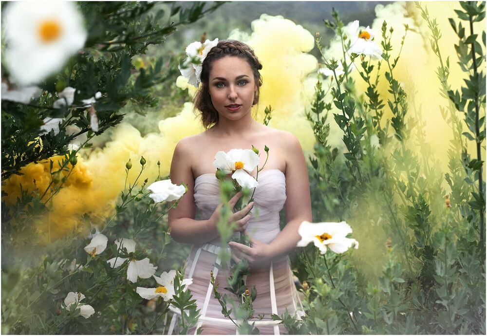 portrait of a girl in santa barbara matilija poppies and surrounded by yellow smoke in fine art creative style