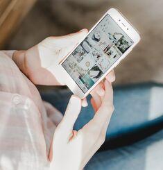 Une personne tient un téléphone intelligent dans ses mains et navigue sur Instagram.