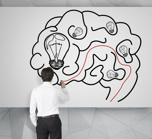 A man stands with his back turned, drawing a brain on a whiteboard.