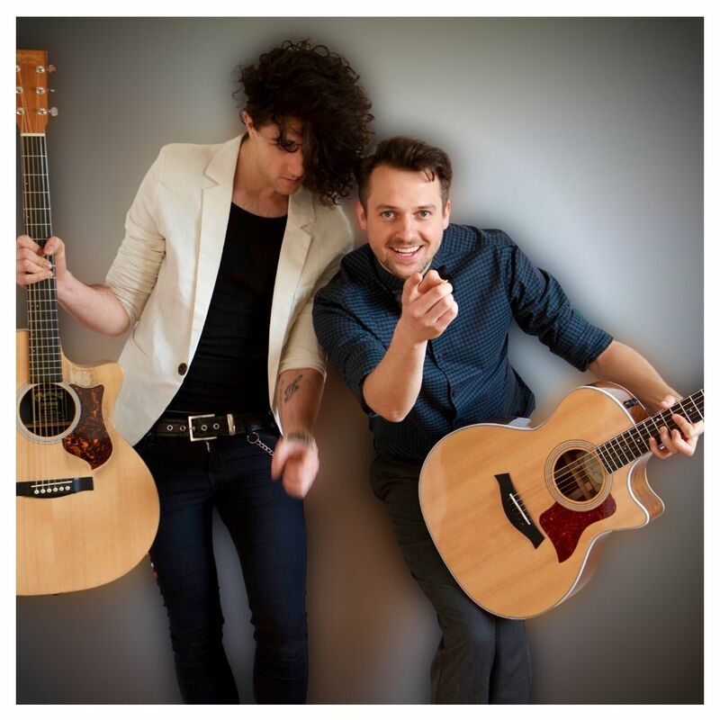 Lonny eagleton is leaning his left shoulder onto Paul Filkes Right shoulder. Lonny is looking down at the ground and Paul is looking and pointing at the camera. Both Paul and Lonny are holding acoustic guitars