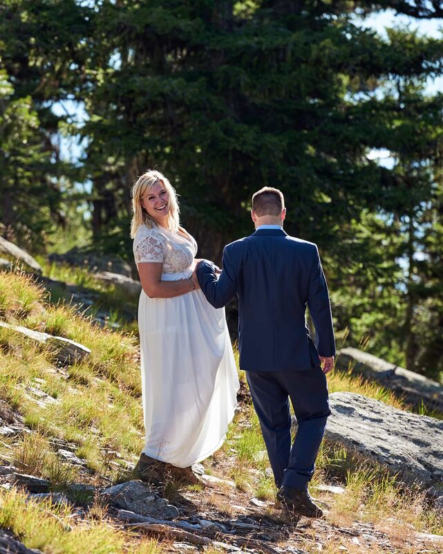 A couple walks hand in hand on a mountain side, through wild grasses and boulders, surrounded by trees. The sun creates a beautiful rim lighting, making them glow. The woman looks back at the camera, flashing a beaming smile.