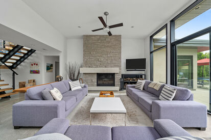 Beautiful living room with stone fireplace and floor to ceiling windows