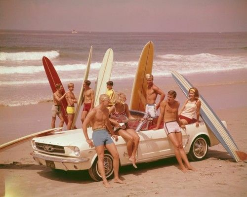 A group of sufers on the beach with a convertible and surfboards in the early sixties