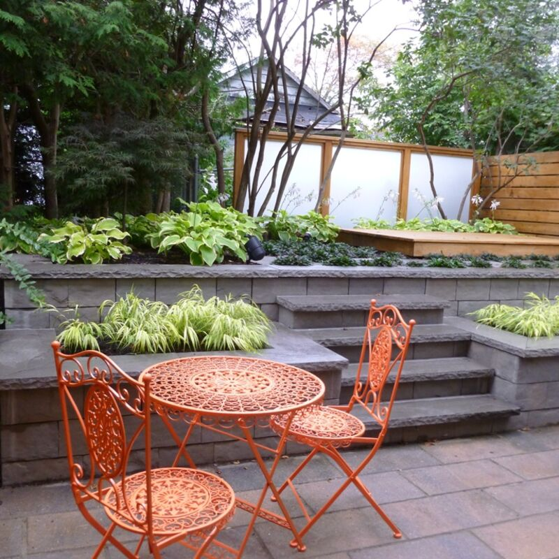 Outdoor patio with centered steps onto a retaining wall