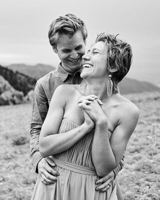 A happy couple hold each other and laugh during a sunrise adventure wedding session in the Bridger mountain range outside of Bozeman, Montana.