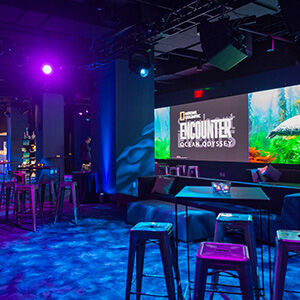 Lobby of National Geographic Encounter with tables, chairs, and projector screen continue to venue page