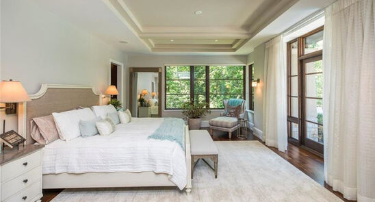 Transitional Master bedroom design with a king bed, wall sconces, and mint accents