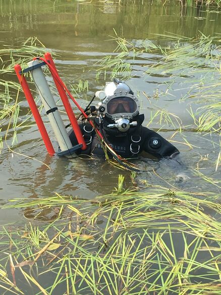 Commercial diver completing underwater pipeline depth of cover inspection