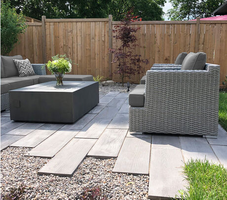 Asian inspired backyards landscape design with grey wicker furniture, techo-bloc borealis pavers and pea-stone accents