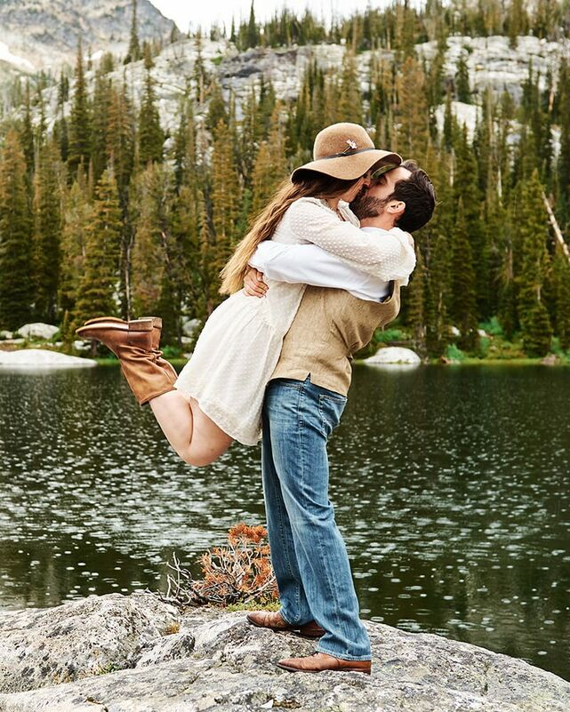 A woman wearing a white dress and brown felted hat leaps into her man's arms, kicking her feet up behind her as they kiss. They stand atop a rock on the shores of an alpine lake surrounded by forest as it begins to rain on an overcast day.