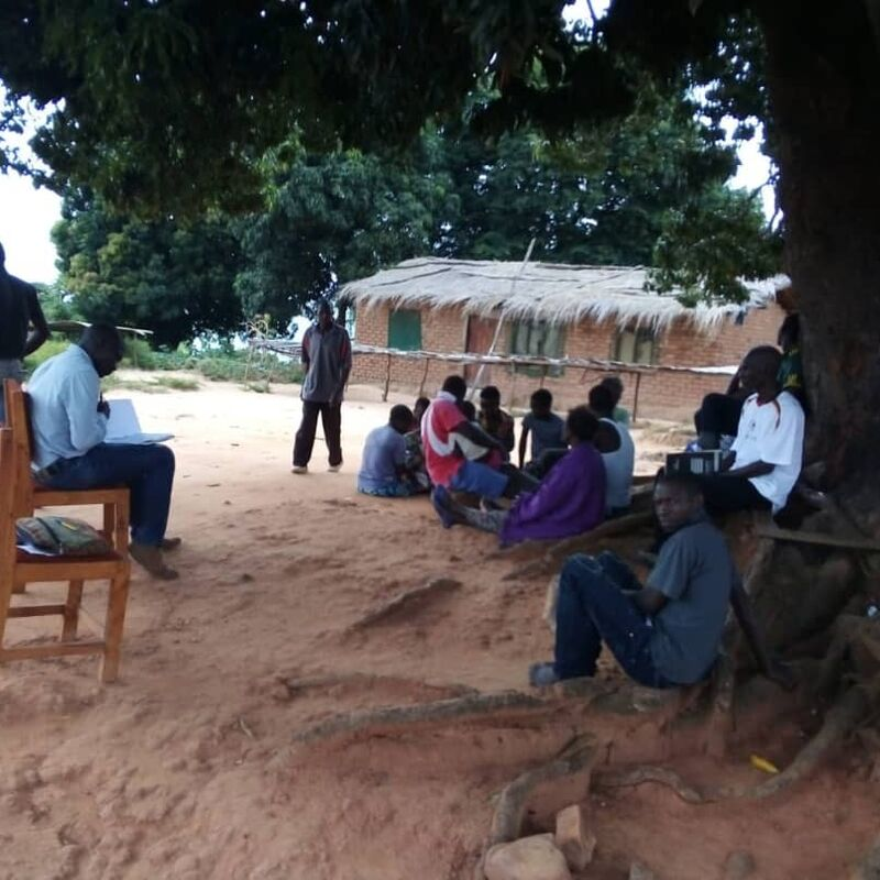 "Village meetings always take place under a big tree in the village center. The tree not only provides shade in the sun, but also protects against rain. Here we informed the village ""Mundola"" about our moring planting project."