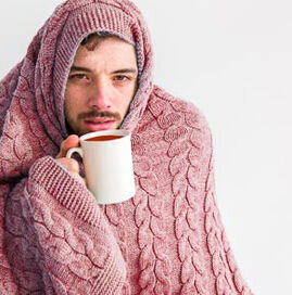man with cold, blanket and coffee for Portland Urgent Care