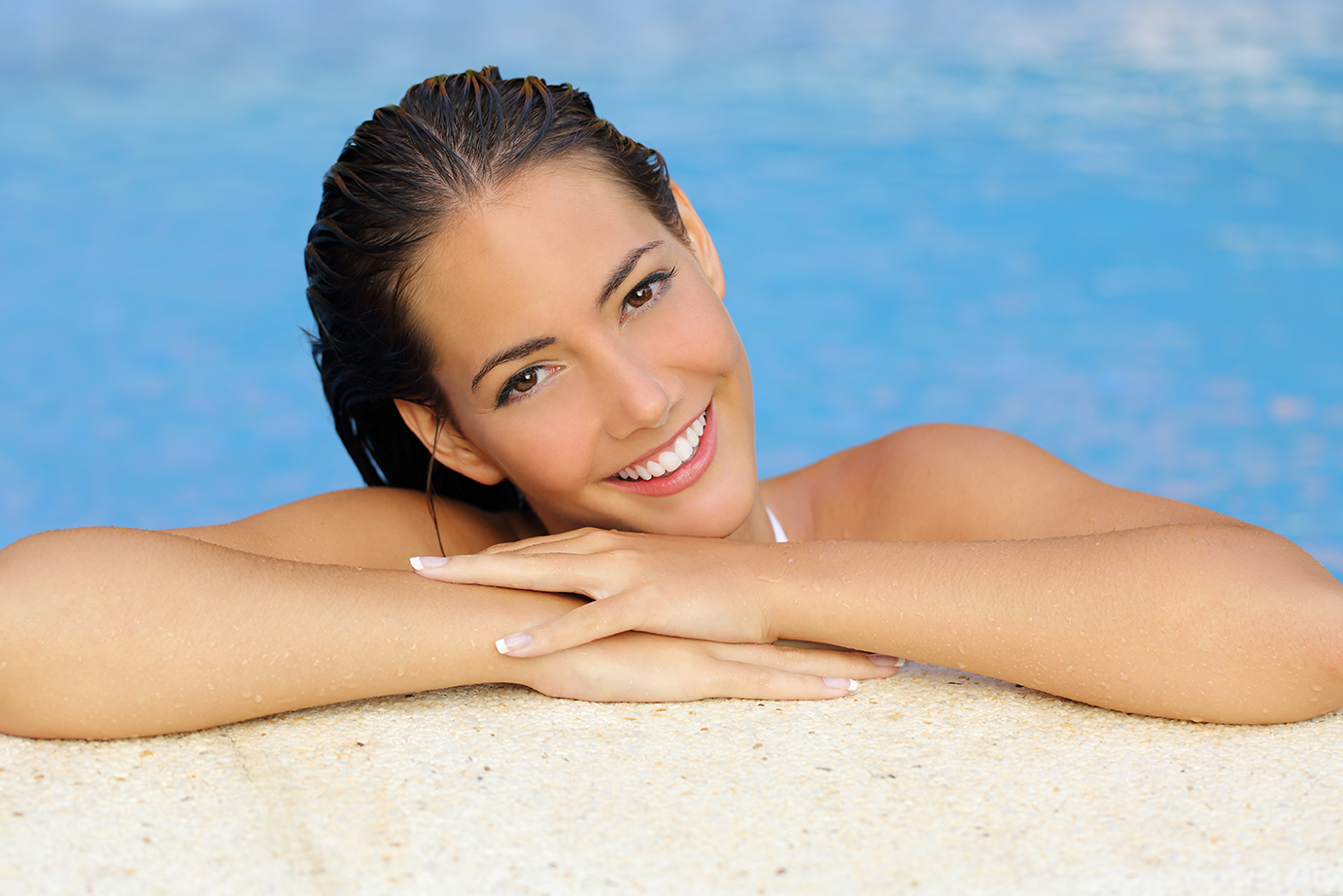 Woman in pool smiling.