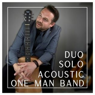"""Promotional Photo of Paul Filek that reads """"Duo, Solo, Acoustic, One Man Band"""" Paul is sitting on a chair holding his baby taylor guitar in front of him facing the camera, while his face looks to your left"""