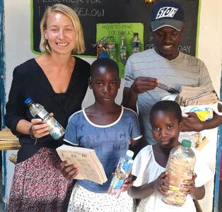 Das Foto zeigt unsere Unterstützerin und freiwillige Helferin Carolina aus Schweden mit Gemeindemitgliedern aus Nkhata Bay, Malawi. Ecobricks werden eingetauscht gegen Stifte & Hefte. Besonders wichtig für SchülerInnen.