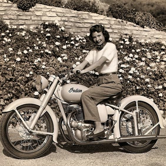 This is a classic vintage foto of a woman motorcycle driver seated on an Indian bike in the 50's