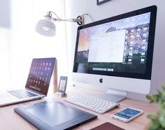 Un macbook et un iMac sur un bureau.