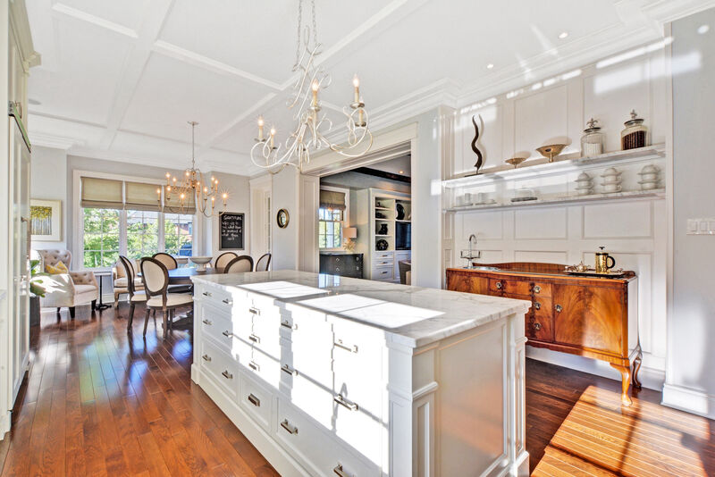 large white painted kitchen, quartz counter tops, marble island, custom coffee bar credenza, and hardwood floors
