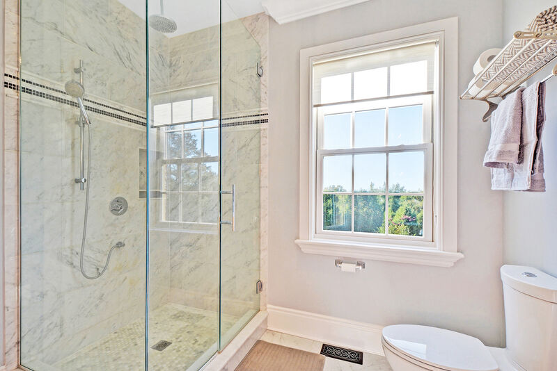 walk-in shower design with large window, brushed nickle fixtures and large wall tiles