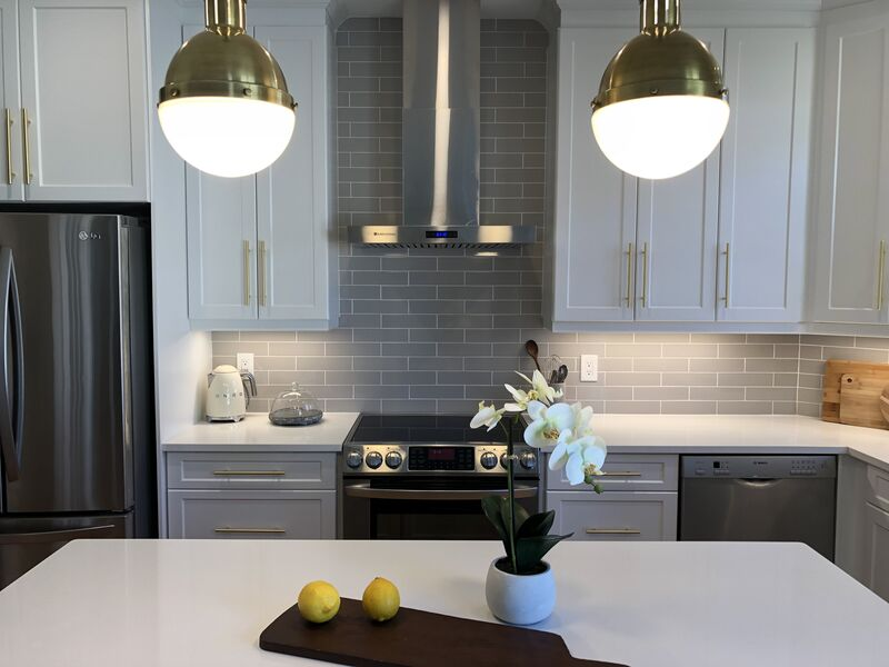kitchen with stainless steel appliances, modern hood fan, brass fixtures, two retro brass pedant lights, quartz counter top  and taupe tile back splash
