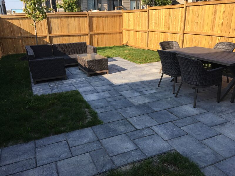 small back yard with perimeter wood fence and modern linear interlock patio