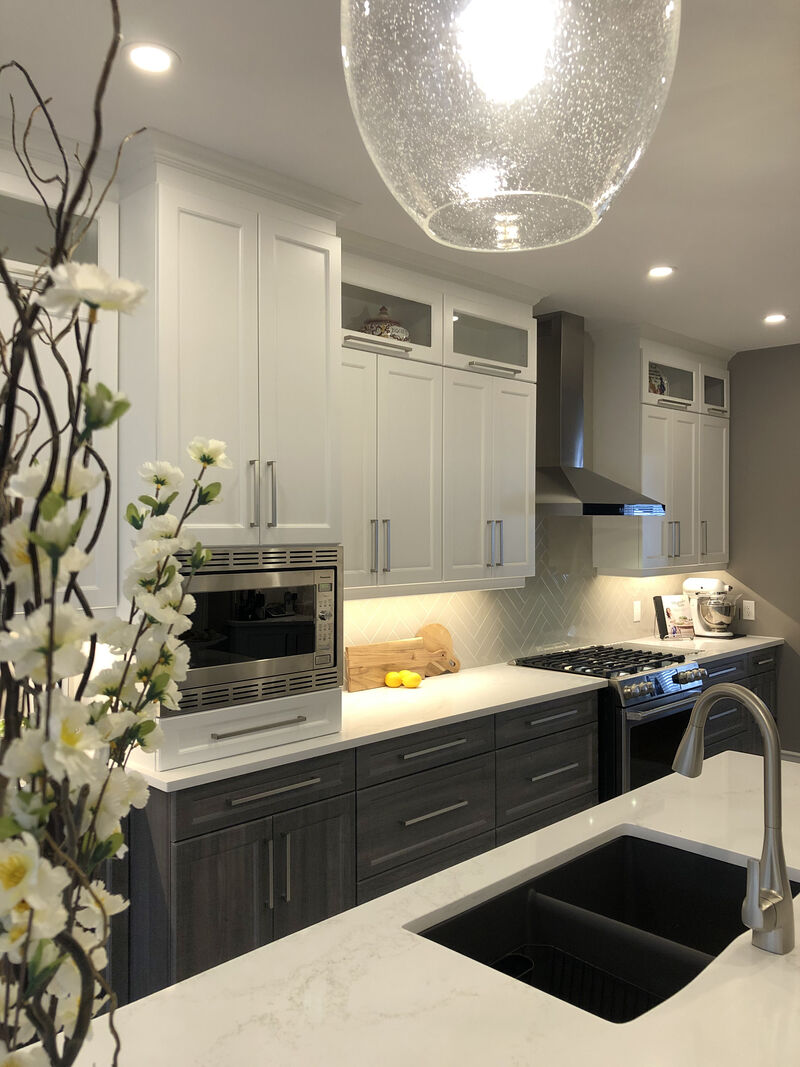 two tone cabinetry with white uppers and dark base cabinetry, white quartz counter-tops and herringbone backslash
