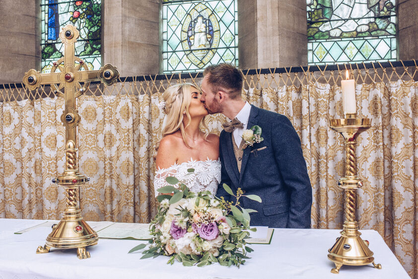 First kiss on the wedding day during a church wedding in Usk, Wales