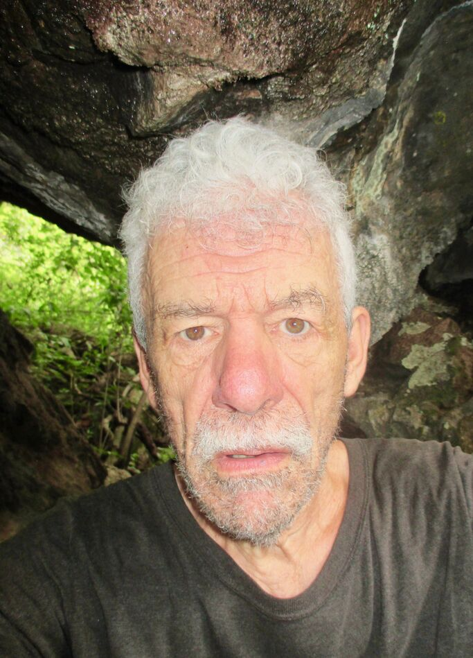 Me --head and shoulders with a large rock in the background. I have curly gray hair, a fuzzy salt and pepper beard/mustache, and brown eyes. Wearing a black t-shirt. I look very serious.