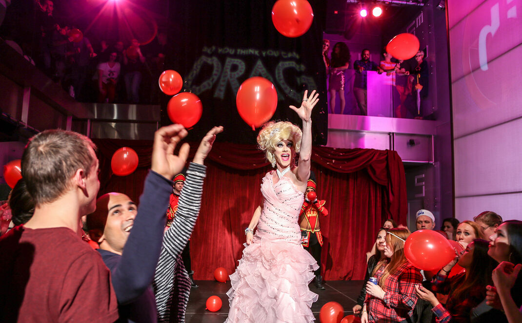 Paige Turner drag queen on stage with balloons at New World Stages