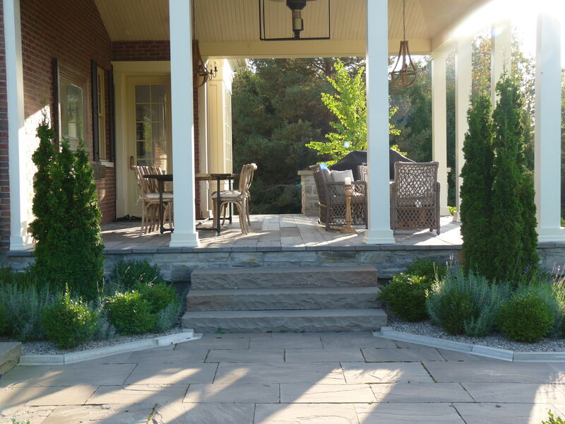 natural stone step leading to spacious covered porch with dining table and soft seating, painted vaulted wood ceiling and wood chandlers