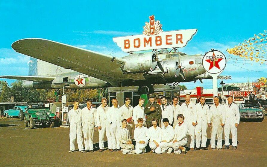 This is a vintage foto of a classic gas station from the fifties using a second world war bomber as a roof emblem of interest to road trip fans and Americana and roadside signs.
