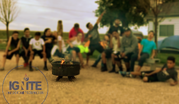 Ignite Youth image - Group of students around a campfire