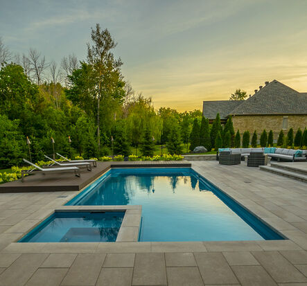 medium size pool and hot tub at dusk with pool loungers on an pvc deck. Soft seating on interlock patio.