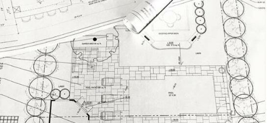 paper copy of printed autoCAD interior design and landscape design plans spread out on a desk