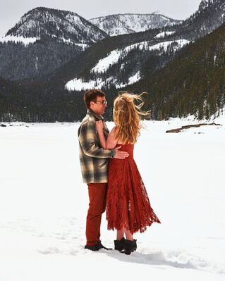 A couple embrace one another amidst a cool winter breeze. They stand on a frozen lake, surrounded by mountains, as the sun shines through the clouds. A light snow falls around them.